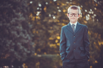 kid businessman with laptop on the park background