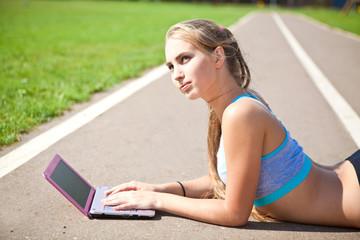 Спортивная девушка с ноутбуком на спортивной площадке
