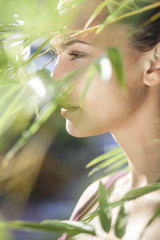 portrait of a beautiful young woman through bamboo leaves