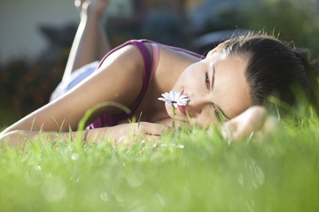beautiful young woman lying on grass and smell flower