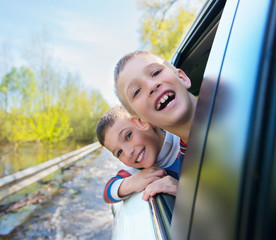 Happy smiling boys looks out the car window.