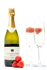 Bottle of champagne with two flutes with floating strawberries