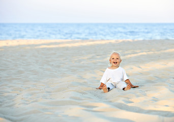 Happy smiling little child sitting on the sunny beach.