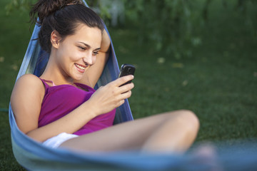 girl using a phone in a hammock in the backyard