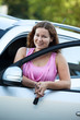 Young woman with ignition key in hand in opened door car