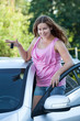 Sexy woman standing over car roof with ignition key