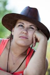 Thoughtful boring Caucasian woman in cowboy hat