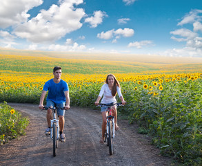 Teen couple riding bike in sunflower field