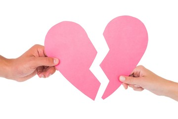 Couple holding two halves of broken heart
