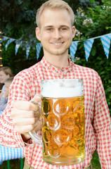 Mann hält Maß Bier bei Oktoberfest Party