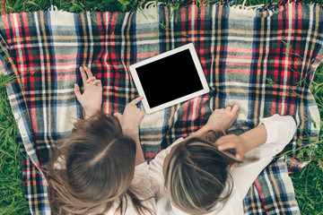 young girls using tablet outdoor
