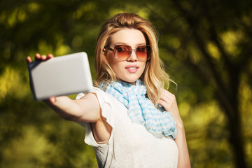 Young fashion woman taking a selfie with tablet computer