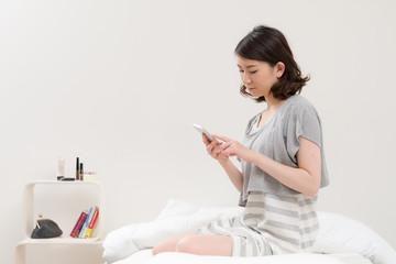 ベッドでスマートフォンを見る女性