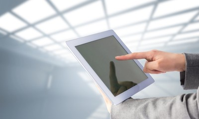 Composite image of businesswoman using a tablet pc