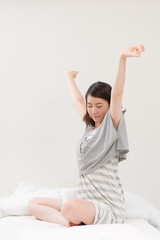 ベッドでストレッチする女性