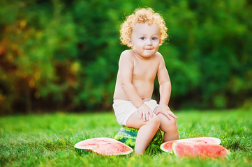 Little child sitting on the grass with a watermelon