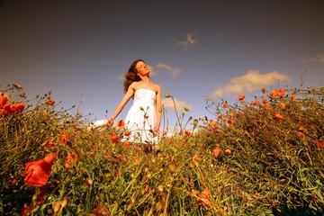Femme dans un champ de coquelicots.