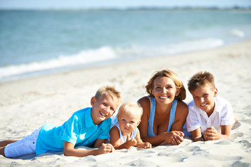 Happymother with children lying on the beach.