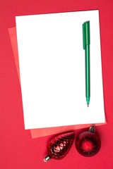 White page with red christmas baubles and pen