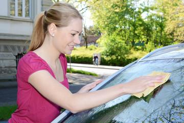 Frau putzt Fenster von Auto