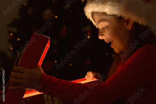 canvas print picture Little girl opening a magical christmas gift