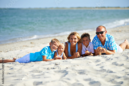 Mother and father with three children on the beach. - 69759472
