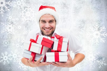 Composite image of festive man holding christmas gifts