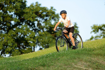 Teenage boy rides a bike from the hill in city park