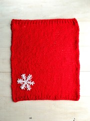 Snow flake on red knitted fabric