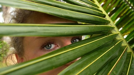 Woman Looking through Coconut Palm Leaves. Slow Motion.