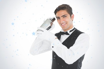 Composite image of handsome barkeeper shaking a drink