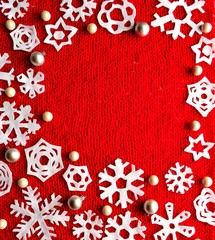 White snow flakes on red knitted fabric background