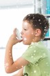 Composite image of boy using asthma inhaler in hospital
