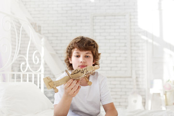 teenager with model paper airlplane in room