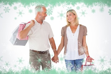 Composite image of happy couple holding shopping bags and hands