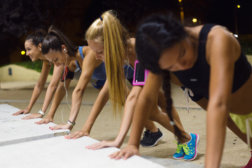 Group of girls doing push-ups at night.