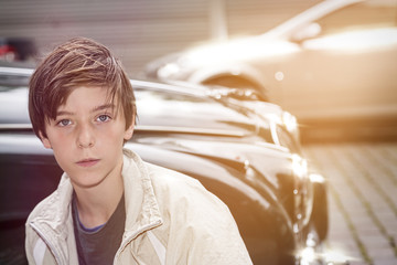 portrait of a teenager boy in front of a old expensive car