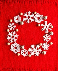 White snow flakes Christmas wreath on red knitted fabric