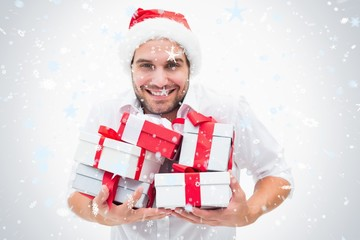 Composite image of handsome festive man holding gifts