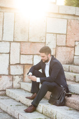 Young businessman using a phone sitting on the stairs