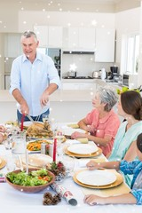 Composite image of senior man serving meal to family