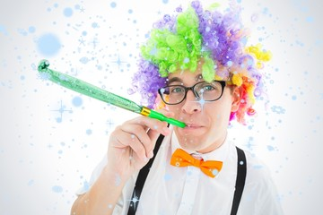 Geeky hipster wearing a rainbow wig blowing party horn