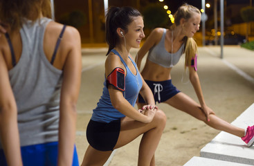 Group of girls doing stretching at night.