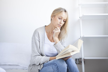 Mature woman sitting on bed reading a book