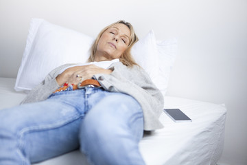 Mature woman having a nap in clothes on bed