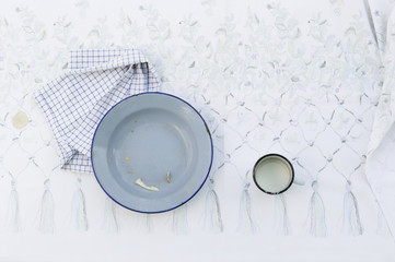empty tin plate and cup on table with tablecloth