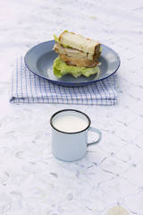 tin cup of milk with sandwich on plate in background