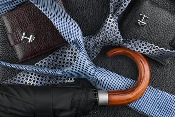 Wallet, tie, cufflinks, umbrella lying on the skin