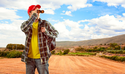 Young man with binocular and backpack camping on nature