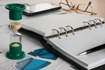 Hourglass, diary, pen, glasses and phone